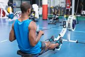 Rear view of African-american fit man exercising on rowing machine in fitness center. Bright modern  poster