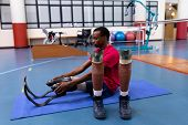Side view of African-american disabled man exercising on exercise mat in sports center. Sports Rehab poster