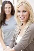 Two beautiful young women friends at home sitting on sofa or settee smiling