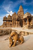 King and lion fight statue and Kandariya Mahadev temple.  Khajuraho, India