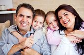 stock photo of daddy  - Portrait of a happy family smiling at home - JPG