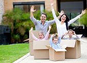 Happy family in cardboard boxes moving house