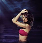 Attractive brunette standing in water