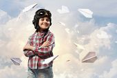 Image of little boy in pilots helmet with paper airplanes in background