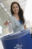 foto of dustbin  - Young woman throwing plastic bottle in dustbin - JPG