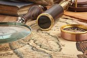 foto of geography  - Vintage brass telescope on antique map - JPG