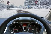 Car drivers view through the vehicle windscreen whilst driving on a snow covered road approaching a roundabout with Give Way signs, the carriageway has one driveable lane formed by previous motorists.