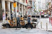 Pessoas passando por carros queimados em Atenas