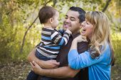 stock photo of three life  - Happy Mixed Race Ethnic Family Having Fun Playing In The Park - JPG