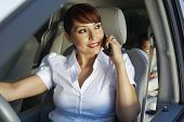 Happy business woman communicating on cell phone with son sitting on backseat