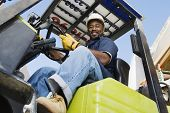 Low angle view of a happy African American industrial worker driving forklift