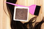 stock photo of hair dye  - hair dye in bowl and brush for hair coloring on beige bamboo mat - JPG