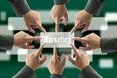 A diverse business team with hands together push Marketing button