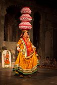 UDAIPUR, INDIA - NOVEMBER 24: Bhavai - famous folk dance of Rajasthan. Performer balances number pots as she dances on the rim of a brass thali (plate). November 24, 2012 in Udaipur, Rajasthan, India