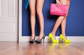 Two girls wearing high heels waiting at the door