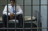 stock photo of outlaw  - Depressed businessman sitting on bed behind a prison gate - JPG