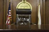 Chair of judge and flags in empty courtroom