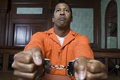 African American prisoner fettered with handcuffs sitting in courtroom