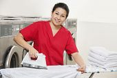 Portrait of a happy woman employee in red uniform ironing clothes in Laundromat