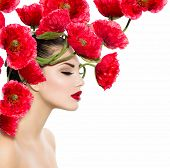 Beauty Fashion Model Woman with Red Poppy Flowers in her Hair. Perfect Creative Make up and Hair Style. Hairstyle. Beautiful Girl. Red Lipstick and Smooth Skin. Isolated on White Background. Nature.