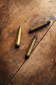 Used fire arm bullet cartridges on a old wooden floor.