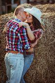couple kissing near hay