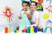 Teacher And Pupil In Pre School Art Class