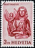 A stamp printed in Switzerland shows Wood Carvings from St. Oswald's Church Zug St. Matthew