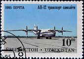 A stamp printed in Uzbekistan shows plane AH-12