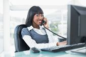 Cheerful businesswoman on the phone while working on computer in bright office