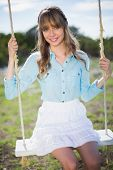 Smiling young model relaxing in a sunny garden sitting on swing