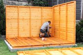 stock photo of wooden shack  - Building a wooden shed and fixing the side panels to the base - JPG