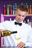 Bartender is pouring white wine into glass