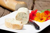 picture of nasturtium  - Homemade nasturtium herb butter on a plate with a piece of baguette on a rustic wooden table - JPG