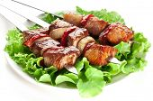 Grilled kebab (shashlik) on spits lettuce leaves.