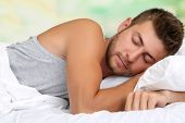 Handsome young man in bed, on bright background, close-up
