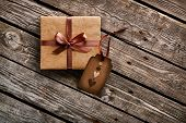 Vintage gift box with gift tag with hearts on old wooden background.
