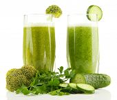 Glasses of green vegetable juice and vegetables isolated on white