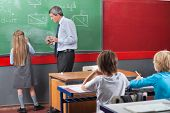 Little schoolgirl solving mathematics on board while teacher looking at her in classroom