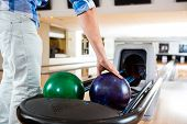 Midsection of man's hand picking up bowling ball from rack in club