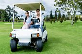 Couple in a golf cart at the course looking very happy