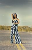 Full length photo of beautiful fashion model wearing pant dress in open desert road