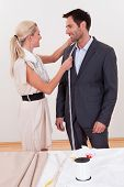 Seamstress Measuring A Man For A Suit