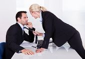 picture of office romance  - Flirting in the office as a beautiful blonde businesswoman pulls a colleague towards her by his tie - JPG