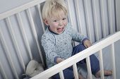 stock photo of crying boy  - Crying boy in bed does not want to go to sleep - JPG