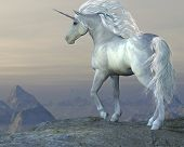 stock photo of unicorn  - A white unicorn stallion looks over his vast territory from a mountain cliff - JPG
