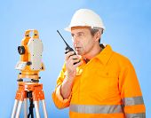 stock photo of theodolite  - Portrait of Senior land surveyor working with theodolite at construction site - JPG