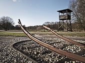 stock photo of ww2  - WW2 concentration camp lookout tower and train track - JPG