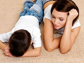 Photo of young mother and its disobedient guilty crying son lying on the floor