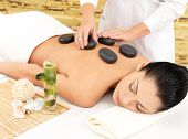 pic of backbone  - Woman having hot stone spa  massage of back in beauty salon - JPG